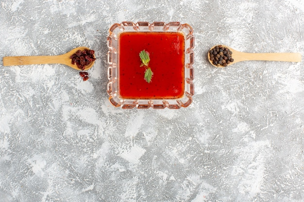 Vista superior de la salsa de tomate fresca dentro de la placa en la mesa gris, cena de comida de sopa