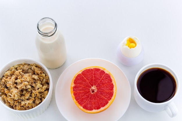 Vista superior saludable desayuno botella de leche, café, harina de avena, huevo duro, pomelo