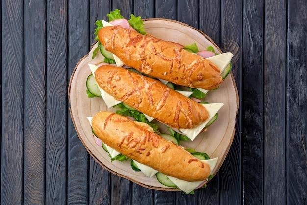 Vista superior de sandwich con jamón, pepino, queso cheddar sobre tabla de madera