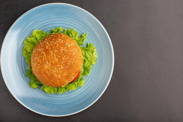 Vista superior del sándwich de pollo con ensalada verde y verduras dentro de la placa sobre la superficie oscura