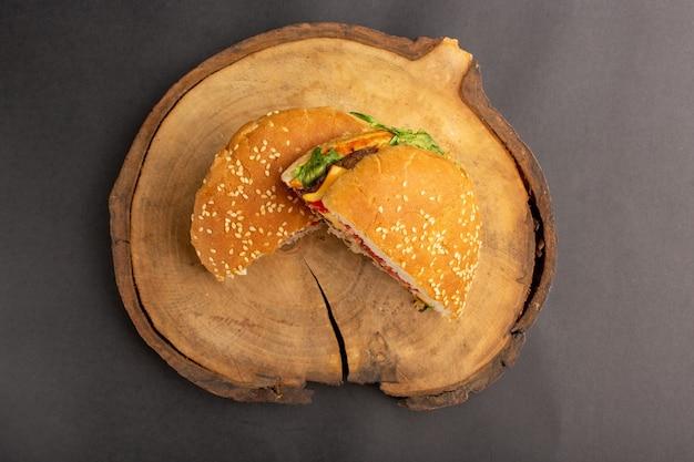 Vista superior del sándwich de pollo en rodajas medio cortado en la superficie oscura