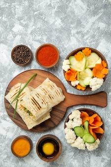 Vista superior de sándwich en rodajas con verduras y condimentos sobre fondo blanco, comida de pan, sándwich, comida de hamburguesa