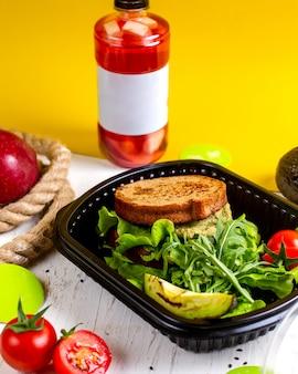 Vista superior de sandwich vegano con aguacate y tomate en una caja de entrega