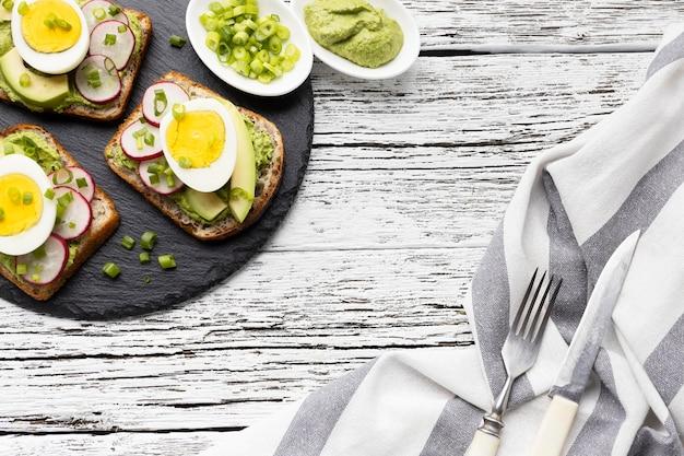 Vista superior de sándwiches con huevo y aguacate en pizarra