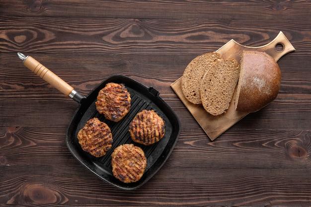 Vista superior de la sartén de hierro fundido con chuletas de ternera y pan integral recién horneado