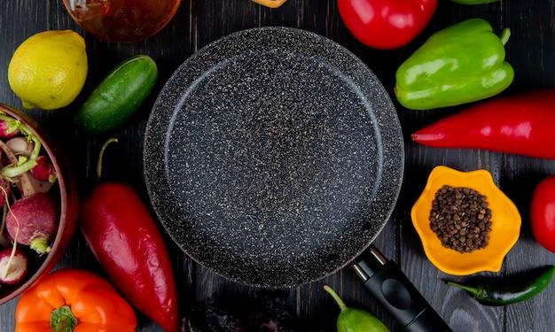 Vista superior de la sartén y verduras frescas coloridos pimientos tomates rábanos pepinos y granos de pimienta negra dispuestos alrededor de la mesa de madera oscura