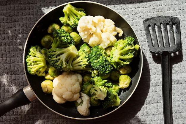 Vista superior de la sartén con verduras frescas descongeladas: coliflor, brócoli, coles de bruselas.
