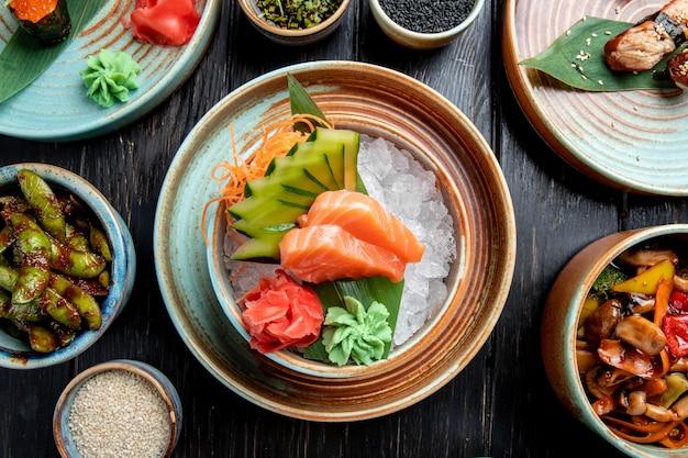 Vista superior de sashimi de salmón con pepinos en rodajas jengibre y salsa de wasabi en cubitos de hielo en un recipiente sobre la mesa de madera
