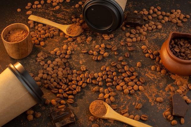 Una vista superior de semillas de café marrón con barras de chocolate y tazas de café