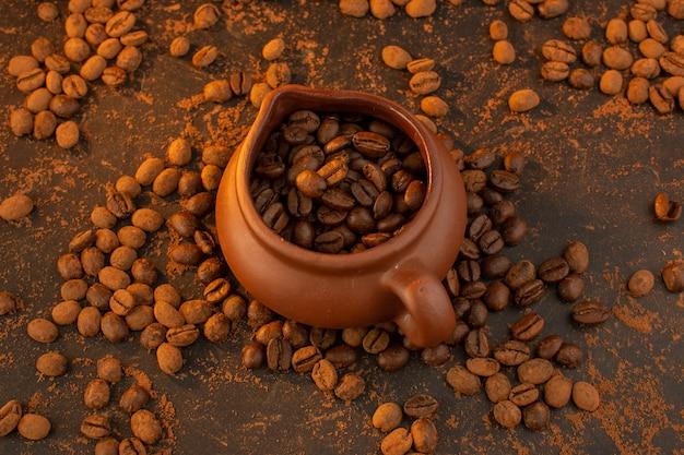 Una vista superior de las semillas de café marrón dentro de la jarra marrón y por toda la mesa marrón
