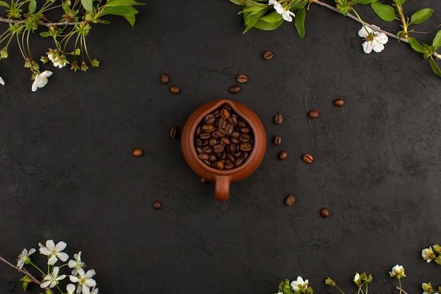 Vista superior de semillas de café marrón entero dentro de una olla marrón alrededor de flores blancas en la oscuridad