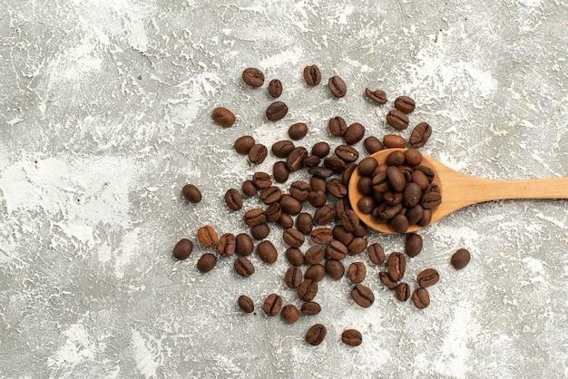 Vista superior de semillas de café marrón frescas sobre fondo blanco granulado de semillas de café