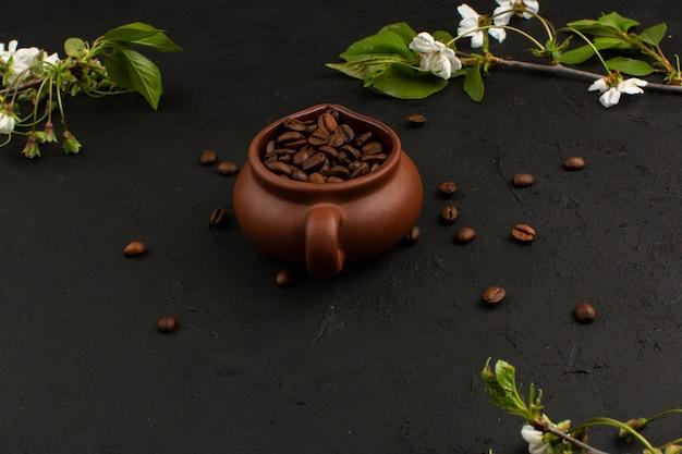 Vista superior de semillas de café marrón junto con flores blancas en la oscuridad