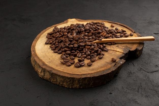 Vista superior de semillas de café marrón en el piso oscuro