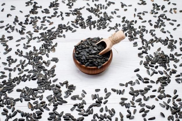 Una vista superior de semillas de girasol negras frescas y sabrosas en todo el fondo blanco, semillas de girasol de grano, merienda
