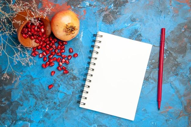 Vista superior de las semillas de granada colocadas en una taza de madera con semillas esparcidas un cuaderno un lápiz sobre una superficie azul