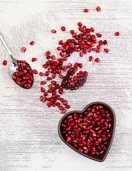 Vista superior de semillas de granada en placa en forma de corazón en la mesa de madera blanca