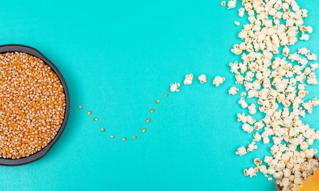 Vista superior de semillas de palomitas de maíz en una bandeja de metal negro a la izquierda y preparada a la derecha sobre fondo azul horizontal