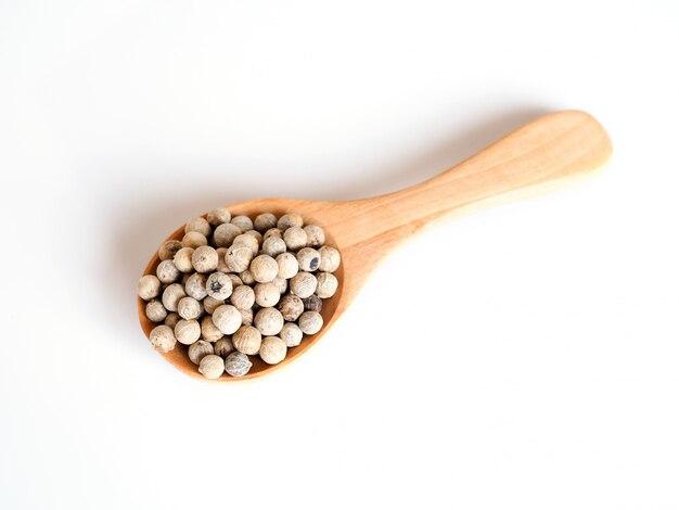 Vista superior de semillas de pimienta blanca en cuchara de madera