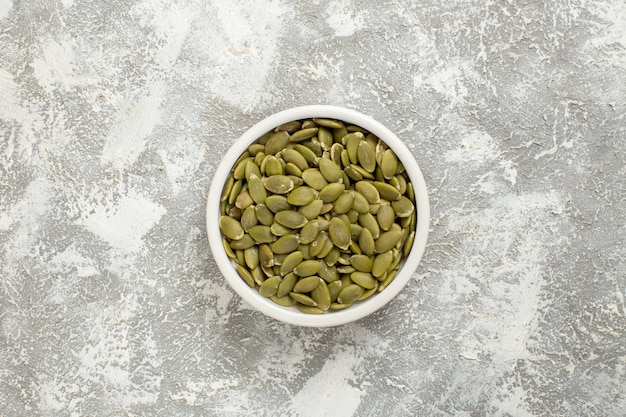 Vista superior de semillas verdes de calabaza sobre fondo blanco semilla verde