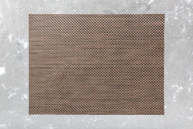 Vista superior de la servilleta de mesa marrón sobre fondo de cemento. mantel individual con espacio vacío