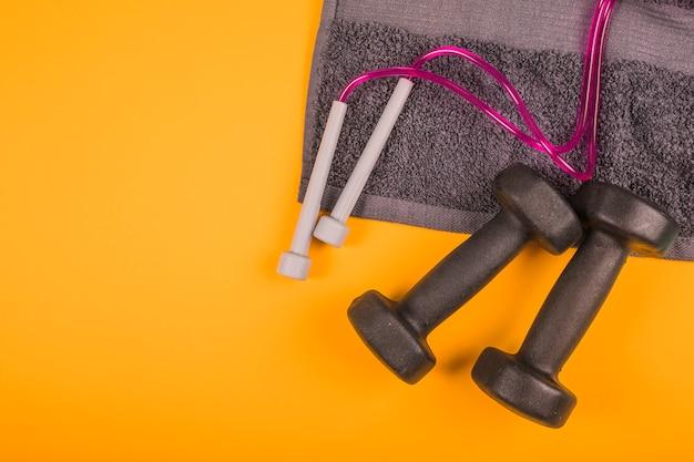 Vista superior de la servilleta con saltar la cuerda y pesas de gimnasia negras sobre fondo amarillo