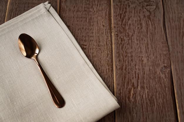Vista superior de la servilleta de tela de color beige y servido cuchara de té en la mesa de madera.