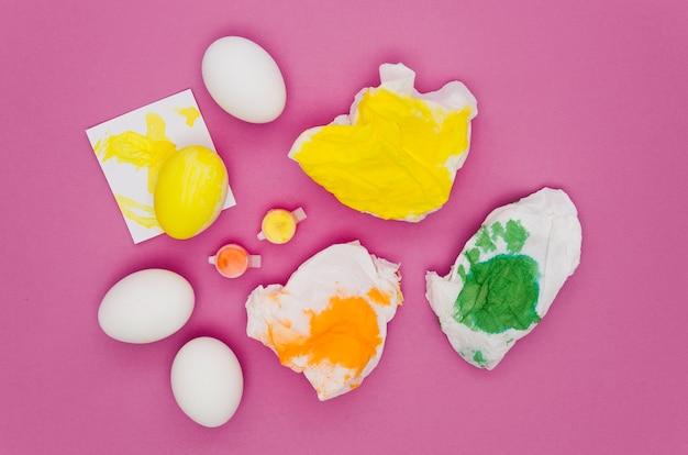 Vista superior de servilletas con pintura y huevos para pascua