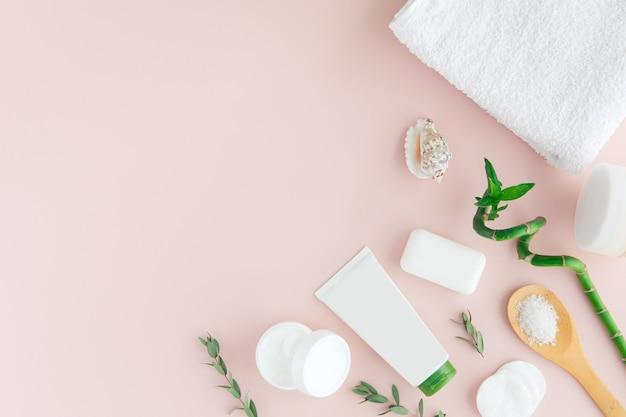 Vista superior del set de cosméticos blanco y verde y hojas para el cuidado de la piel facial y tratamiento de spa con bambú en rosa