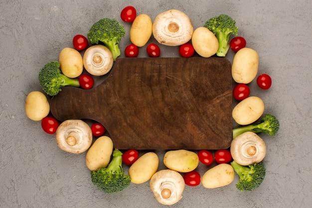 Vista superior setas brócoli patatas frescas maduras en el gris