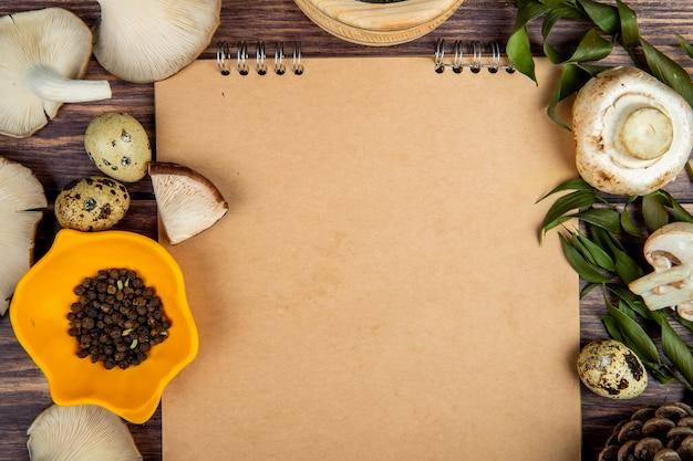 Vista superior de setas frescas, granos de pimienta negra, huevos de codorniz dispuestos alrededor de un cuaderno de bocetos en madera rústica
