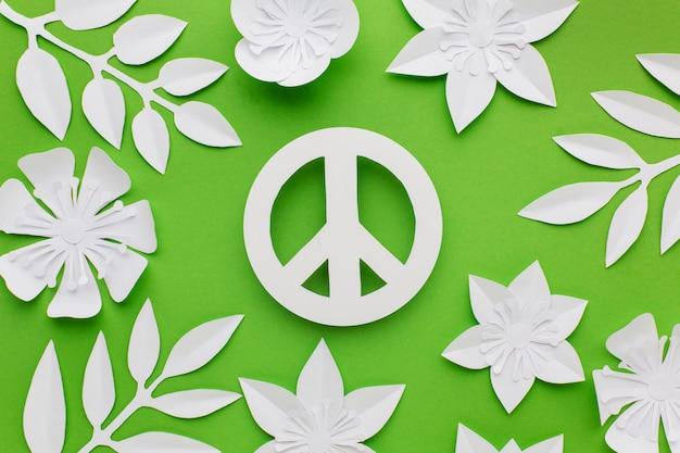 Vista superior del signo de la paz de papel con hojas y flores.