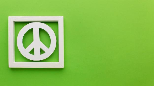 Vista superior del signo de la paz de papel en el marco con espacio de copia