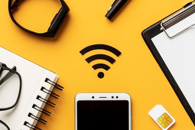 Vista superior del símbolo de wi-fi con teléfono inteligente y tarjeta sim