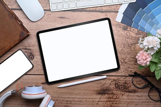 Vista superior simulacro de tableta digital, lápiz óptico, pila y teléfono móvil en el espacio de trabajo del diseñador gráfico.