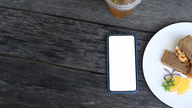 Vista superior del simulacro de teléfono inteligente con pantalla en blanco y pastel en la mesa de madera en el café.