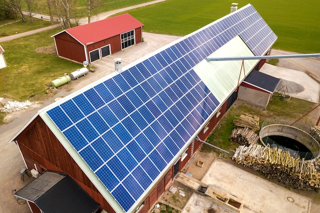 Vista superior del sistema de paneles fotovoltaicos solares azules en el edificio de madera, granero o techo de la casa. producción ecológica renovable de energía verde.