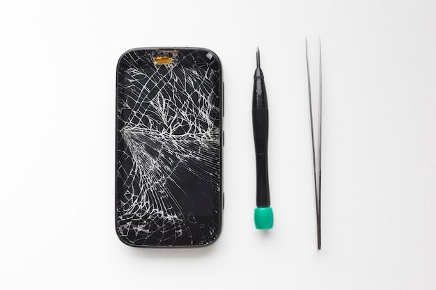 Vista superior smartphone roto con herramientas de reparación