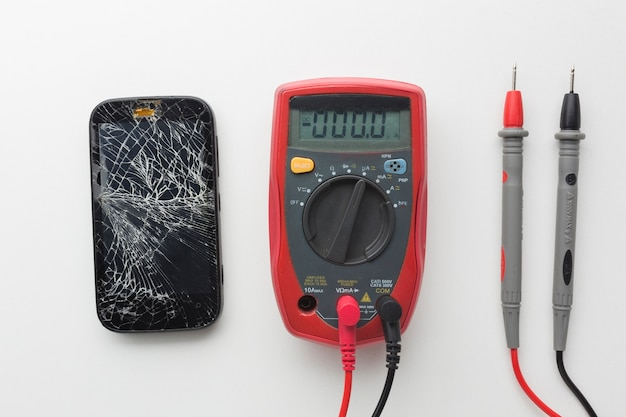 Vista superior smartphone roto con multímetro