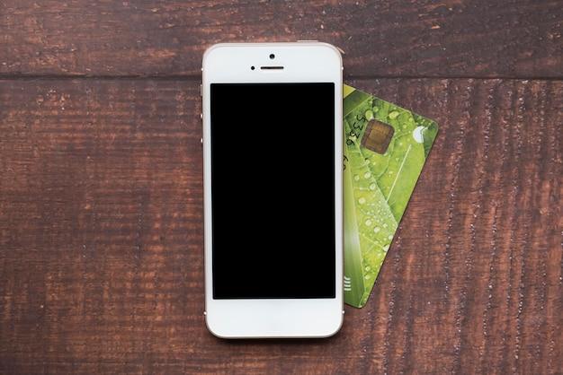 Vista superior smartphone con tarjeta de crédito