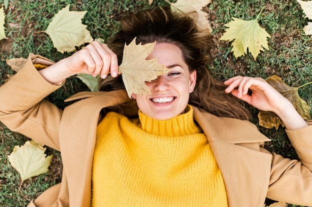 Vista superior smiley joven permanecer en el suelo junto a las hojas de otoño