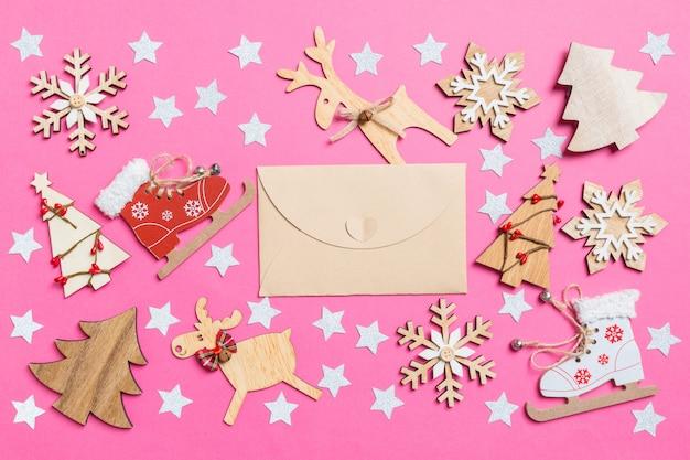 Vista superior del sobre artesanal decorado con juguetes festivos y renos y árboles de navidad. concepto de vacaciones