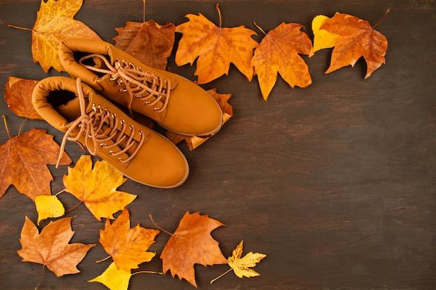 Vista superior sobre las botas naranjas de otoño y las hojas de otoño