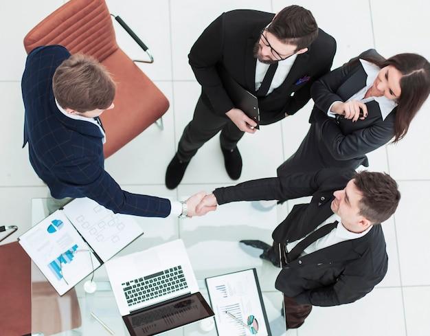 Vista superior: socios comerciales de apretón de manos confiables después de la discusión del contrato financiero en la oficina