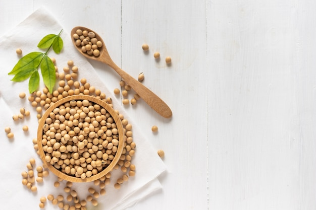 Vista superior de soja o soja en un tazón sobre madera blanca