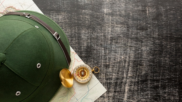 Vista superior sombrero y brújula en una mesa
