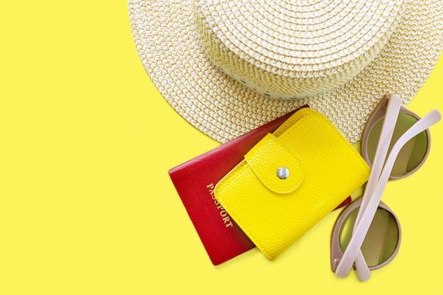 Vista superior del sombrero, gafas de sol y pasaporte con bolso de cuero. fondo de vacaciones de verano. verano, viajes, playa, concepto de turismo. fondo amarillo con espacio de copia.