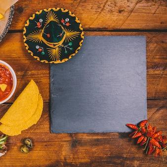 Vista superior del sombrero mexicano; salsa de salsa tortilla; pizarra negra y chiles rojos sobre banco de madera