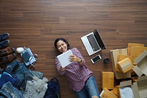 Vista superior sonriente a mujer asiática tendido en el piso de madera y escribiendo en el cuaderno