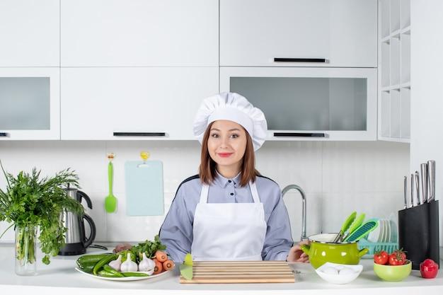 Vista superior de la sonriente chef femenina y verduras frescas en la cocina blanca